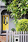 Entrance area with yellow front door and front garden with gray picket fence