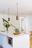weiße Kücheninsel mit Ananas und Lilienstrauss, darüber DIY-Pendelleuchten aus Windlichtern