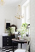 Console table below window and black chest of drawers in bathroom with white subway wall tiles