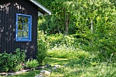 Wooden house with blue lattice window surrounded by summer garden