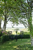 Seating area in idyllic summer garden with view of landscape