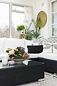 Bowl with colourful planting on black wicker coffee table in front of cosy couch