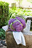Arrangement of alliums and rushes on stone trough