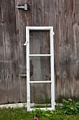 Old lattice window leaning against weathered wooden wall