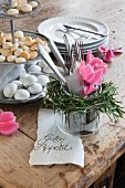Pink cyclamen and rosemary wreath around cutlery in glass pot on rustic wooden table