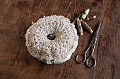 Vintage crocheted pin cushion, scissors and reels of thread on wooden table