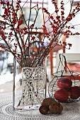Autumnal arrangement of pine cones, wire basket and branches of red berries in glass vase decorated with crocheted doilies on table