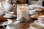 Candle lantern decorated with crocheted doily on table set for tea