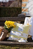 Hand-sewn cushion cover with pattern of butterflies next to daffodils on weathered garden bench