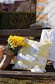 Selbst genähte Kissenhülle mit Schmetterlingsmotiven, neben Osterglocken auf verwitterter Gartenbank