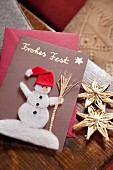 Hand-made Christmas card with picture of snowman wearing Father-Christmas hat