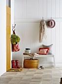 Garderobe an weiß lackierter Holzwand, Sitzbank mit Kissen und Aufbewahrungsdosen