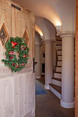 Festive wreath on open, rustic front door and view into hallway with columns and arched ceiling