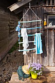 Hand-made towel rack made from sticks painted in shades of blue hung outside boat house