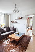 Grey sofa and coffee table on patchwork animal-skin rug in living room