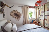 Small bedroom with animal skin and horn on wall and patchwork wallpaper on sliding door