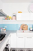 White fitted kitchen with pale blue wall tiles, wall cabinets and storage jars on shelf