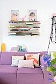 Scatter cushions on lilac couch below bookshelves