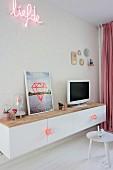 weiße Hängeschrank mit Fernseher und gerahmtem Bild vor Tapete mit Leuchtschrift