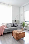 Pink blanket and various scatter cushions on pale grey couch behind vintage wooden crate used as coffee table
