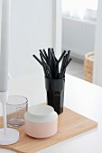 Black drinking straws, china pot, glass and candlestick on wooden chopping board