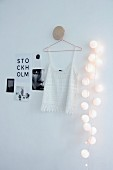 Spherical fairy lights next to white lace top and black and white pictures on wall