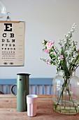 Blumen in Glasvase und Thermoskanne mit Becher auf Holztisch, Sehtafel an der Wand