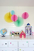 Colourful paper pompoms hung on white wood cladding above toys on chest of drawers in girl's bedroom