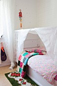 Colourful crocheted blanket, retro rose-patterned rug and child's white bed with canopy