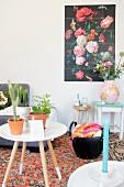 Beistelltisch mit Zimmerpflanzen vor Tasche mit Häkelarbeit, Vintage-Hocker mit Vase und buntem Blumenbild