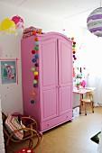 Pinkfarbener Kleiderschrank mit bunten Kugelgirlanden dekoriert in Mädchenzimmer