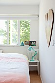 Turquoise retro lamp on white wooden chair used as bedside table below open window