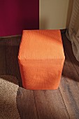 Hand-made cardboard pouffe with orange cover