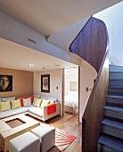 Curved staircase with solid wooden balustrade in living room