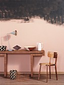 Ornaments on wooden console table and metal chair against wall painted pink and smudgy black