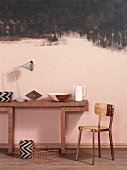 Wandtisch aus Holz mit Dekoobjekten und Metallstuhl vor rosa getönter Wand mit schwarzen Farbspuren