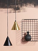Two pendant lamps, one with a brass lampshade, one with a black lampshade, next to vase in wire basket mounted on wall painted pink and smudgy black