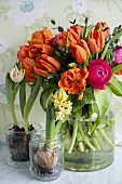Orange tulips and pin ranunculus in glass vase next to hyacinth and tulips planted in glass pots