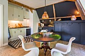 Shell chairs at round dining table in modern kitchen with rustic wooden floor