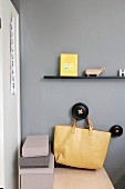 Narrow black floating shelf above yellow bag hung from black peg on grey wall