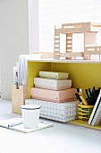 Architect's model above cardboard boxes and pen holder in yellow shelf unit with notebook and beaker on table in front