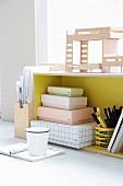 Architekturmodell auf gelbem Regal mit Pappkartons und Stiftehalter, davor Notizbuch und Becher