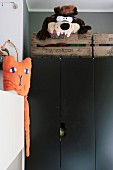Soft toy in rustic wooden crate on black cupboard and orange cat on white cabinet to one side