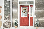 Woman peeping out of open front door on snowy day