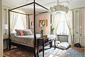 Bed with wooden frame in romantic bedroom with pastel pink walls annd floral home textiles