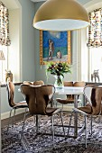 Classic chairs with animal-skin covers around round dining table in corner