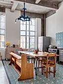 Offene Küche mit Ornamentfliesen und eklektischer Einrichtung vor hohen Industriefenstern