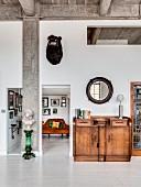 Wohnbereich mit Betondecke, eklektischer Einrichtung und weisser Dielenboden in Loftwohnung