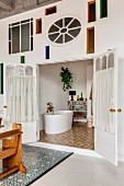 Wall with artistic stained-glass elements and view of white. free-standing bathtub in bathroom