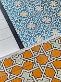 Various floor coverings: white wooden floor, ornate blue and white tiles and ochre tiles with geometric pattern
